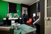 The living room is a time capsule and the dramatic green and black colour scheme the perfect backdrop for a stunning collection of art and furniture