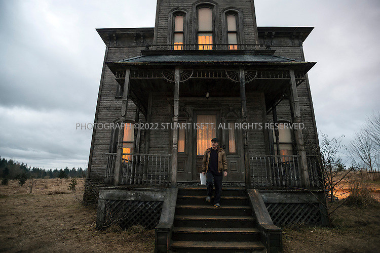 "1/28/2013--Aldergrove, British Columbia, Canada..New York Times report Neil Genzlinger on the set of ""Bates Motel"", an upcoming television series on A&E. The series is inspired by Alfred Hitchcock's Psycho, and will depict the life of Norman Bates (played by Freddie Highmore) and his mother Norma (played by Vera Farmiga) prior to the events portrayed in Hitchcock's film. A&E chose to skip a pilot of the series, and ordered a 10-episode first season. The series was filmed in Aldergrove, British Columbia, close to the US border and near Vancouver. It's scheduled to debut in March...Here: Neil on the stairs leading to the main house. the roof was not built for the first season and will be added digitally in post production...©2013 Stuart Isett. All rights reserved."