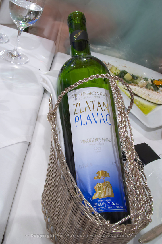 Bottle of wine in a silver wine basket cradle, 2005 Zlatan Plavac Vrhunsko Vino Vinogorje Hvar Sveta Nedjelja, Zlatan Winery from the luxury Excelsior Hotel and Spa restaurant terrace Dubrovnik, old city. Dalmatian Coast, Croatia, Europe.