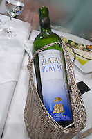 Bottle of wine in a silver wine basket cradle, 2005 Zlatan Plavac Vrhunsko Vino Vinogorje Hvar Sveta Nedjelja, Zlatan Winery from the luxury Excelsior Hotel and Spa restaurant terrace Dubrovnik, old city. Dalmatian Coast, Croatia, Europe.