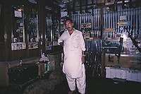 The owner of one of the many gun shops in Darra, in the tribal area near the Khyber Pass in Pakistan, stands proudly in front of his wide ranging stock of counterfeit but fully functional weapons.