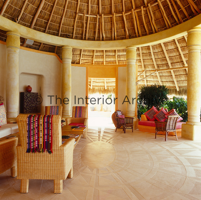 A curved thatched roof or palapa covers this open plan living area