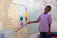 Jambiani, Zanzibar, Tanzania.  Young Student Points to the Namers of the Days of the Week in Swahili.  The same chart shows them in English and in Arabic.