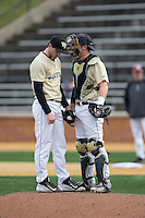 Wake Forest Demon Deacons catcher Ben Breazeale (9) has a chat on the mound with starting pitcher Connor Johnstone (3) during the game against the Harvard Crimson at David F. Couch Ballpark on March 5, 2016 in Winston-Salem, North Carolina.  The Crimson defeated the Demon Deacons 6-3.  (Brian Westerholt/Four Seam Images)