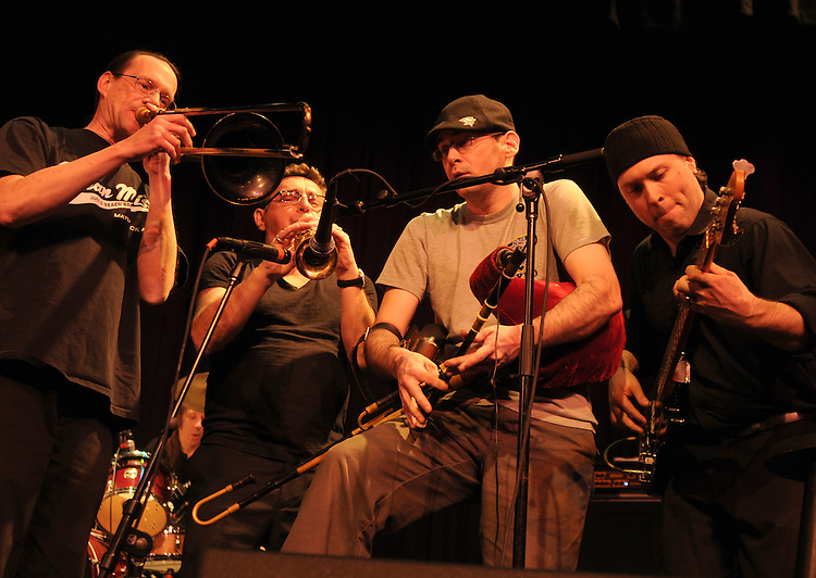 Left to right: Fred Parcells (Trombone & Penny Whistle), Geoff Blythe (Saxophone), Joseph Mulvanerty,(Uilleann Pipes & Flute), and Joe Burcaw (Bass) of Black 47, jamming during a performance at the Boulton Center in Bay Shore, Long Island, on Friday, March 4, 2011. Photograph by Jim Peppler. Copyright Jim Peppler/2011.