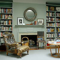 A distressed leather armchair next to the fireplace in the study provides a comfortable reading place