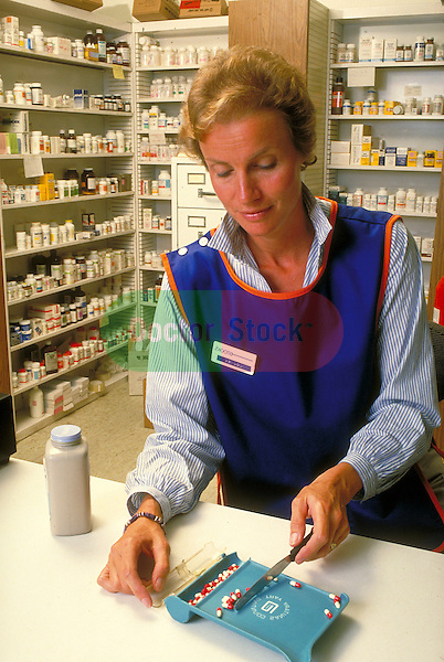 female pharmacist counting dosage of pills
