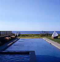 A long swimming pool stretches away from the house towards the ocean