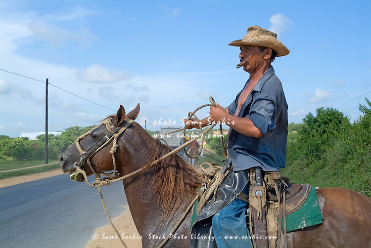 Cowboy smoking a cigar while riding his horse on a rural road in Cuba.