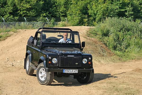 Germany, Bad Kissingen, Allrad Messe, 15-18.06.2006. Sebastian Fasold of Land Rover Germany demonstrating a special edition Land Rover Defender 90 TD5 Cabriolet. --- No releases available. Automotive trademarks are the property of the trademark holder, authorization may be needed for some uses.