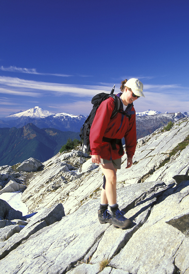 Hiker in red jacket scrambling up rocky slabs, Mt Baker in background, North Cascades National Park, Washington