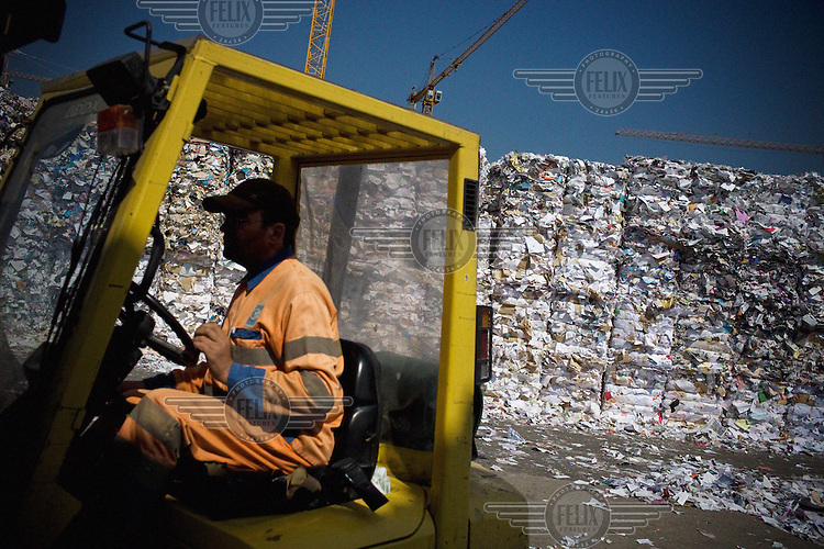 A worker manouvres a forklift vehicle at a paper recycling centre in Paris.