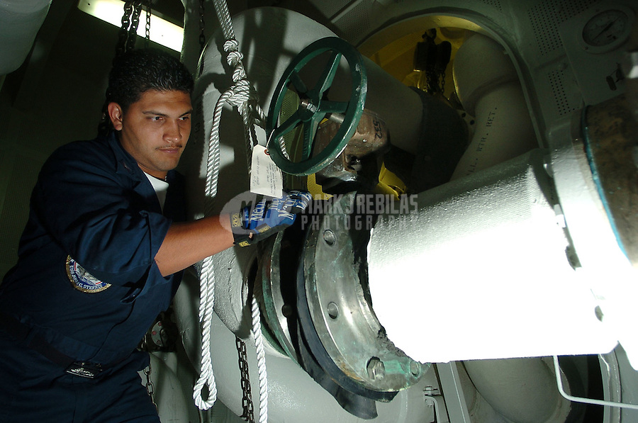 "040709-N-6213R-038 Pacific Ocean (July 9, 2004) - Machinist's Mate 3rd Class Raphael Lara of Los Angeles, Calif. works to remove a water line from the number nine air conditioning condencer deep within the confines aboard USS John C. Stennis (CVN 74).  Debris occasionally gets sucked into the water pipes when a ship is in shallow water and needs to be removed.  Stennis and Carrier Air Wing Fourteen (CVW-14) are taking part in the multi-national maritime exercise ""Rim of the Pacific 2004"" (RIMPAC).  RIMPAC is the largest international maritime exercise in the waters around the Hawaiian Islands.  This year's exercise includes seven participating nations; Australia, Canada, Chile, Japan, South Korea, United Kingdom and United States.  RIMPAC is intended to enhance the tactical proficiency of participating units in a wide array of combined operations at sea, while enhancing stability in the Pacific Rim region.  Photo by Mark J. Rebilas"