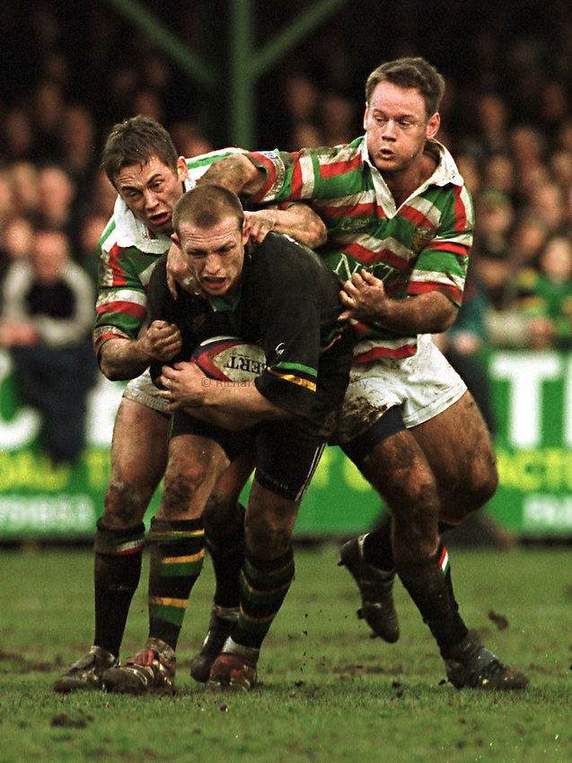 Photo. Richard Lane. .Northampton v Leicester. 13/3/99. .Matt Dawson is caught by Jamie Hamilton and Pat Howard.