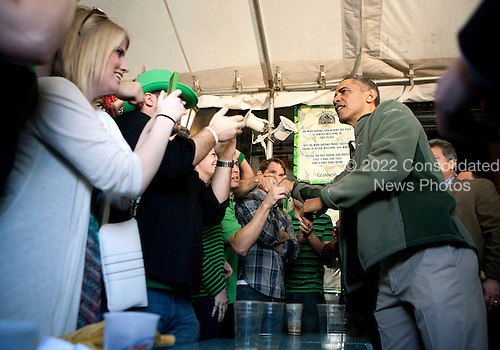 United States President Barack Obama (R) greets patrons as he visits a bar in celebration of St. Patrick's day at the Dubliner Restaurant and Pub on March 17, 2012 in Washington, DC. Next week, Obama and Vice President Biden will meet the Irish Prime Minister Enda Kenny and attend a St. Patrick's Day lunch at the Capitol. .Credit: Joshua Roberts / Pool via CNP