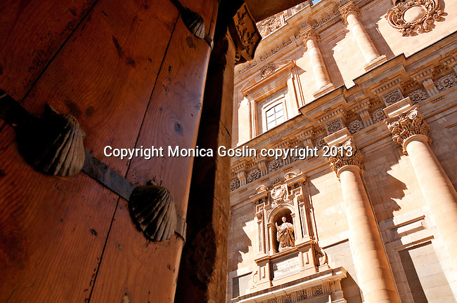The large wooden door of the Casa de las Conchas, covered with shells and a view of the University of Salamanca building in the background; The University of Salamanca is the oldest University in Spain, it was founded in 1218