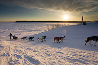 As the sun rises over frozen Yukon River Jessica Hendricks arrives in Kaltag 2006 Iditarod Western AK