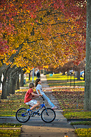 Friends share a bike as they travel to a nearby park on a fall day