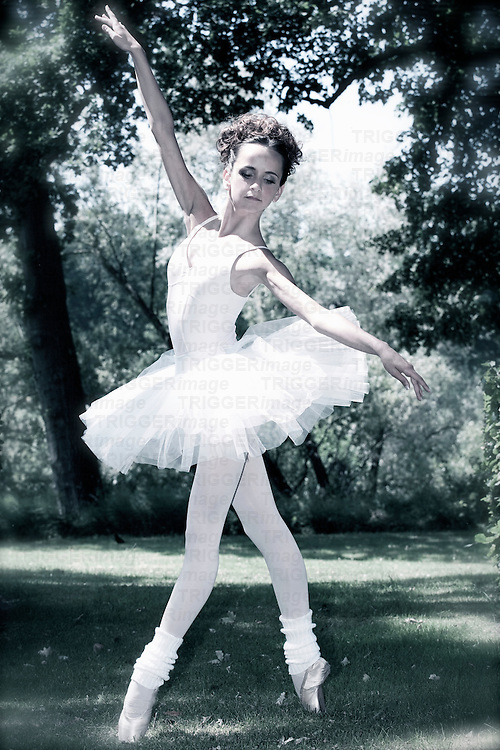 Female youth with wearing white ballet dress standing on point outdoors