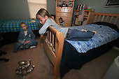 Sophia Salem 8 of Telford, Pa., and twin to Joseph (in background), watches as her brother Sam 13 plays with a remote control dog in his and twin brother Jake and younger brother Joseph's  bedroom on a cold Thursday March 2, 2006. The American flag hangs in the boys bedroom. The Salem children, 3 sets of twins, are from Russia. Sophia and twin Joseph were adopted at 11 months of age by Hythem and his wife Lisa. The other twins, Selene and Julianne 13 along with Sam and Jake, were adopted just 20 months ago. All children are thriving in school, socially and physically. photo by jane therese