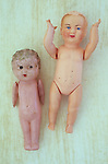 Small celluloid naked boy and girl dolls with moving arms and legs and pinholes lying on rough board