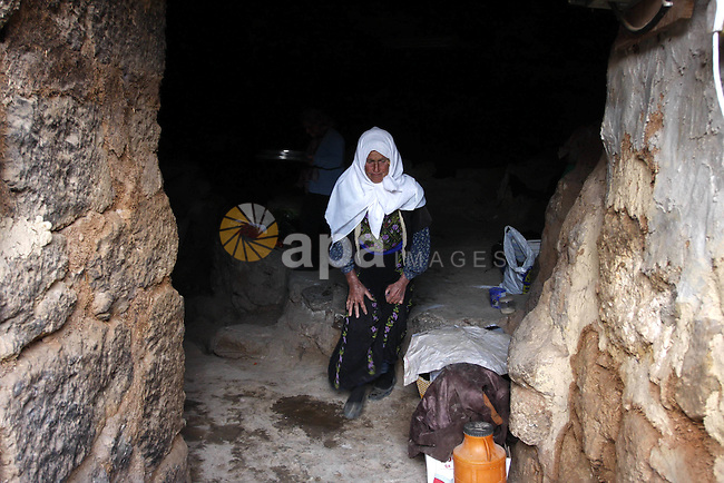 Palestinian woman stands inside a cave in a mountainous area outside the city of Hebron in the occupied West Bank on May 22, 2010. Photo by Mamoun Wazwaz