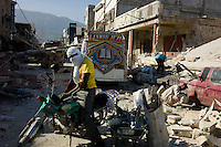 Port au Prince, Haiti, January 15 2010.The downtown area has been one of the most severely damaged in the earthquake. Most of the buildings are almost completely destroyed; it is a popular small shops area near the Hyppolite market, so many people are trying to find goods in the ruins; hte police patrols and shoots on sight if anyone is carrying a weapon.