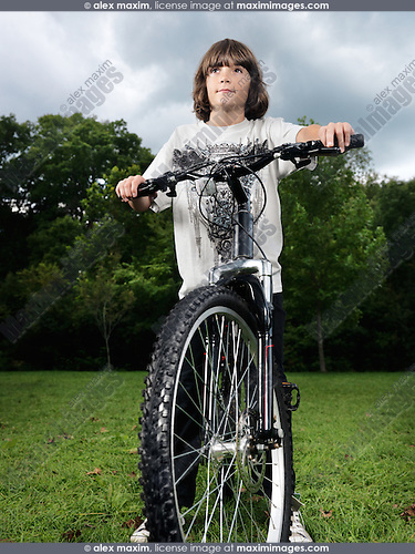 Artistic dramatic portrait of a ten year old boy standing with a bicycle in the nature