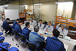 February 20, 2012, Fukushima, Japan - Nuclear and Industrial Safety Agency (NISA) security inspectors, rear, talk with TEPCO workers, front, in a power room equipped with beds, on Feb. 20, 2012, in Okuma, Fukushima Prefecture.