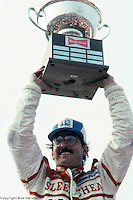 Bobby Rahal celebrates with the trophy in victory lane after winning the Grand Prix of Cleveland, the first victory of his IndyCar career, on July 4, 1982, at the Burke Lakefront Airport temporary course in Cleveland, Ohio.