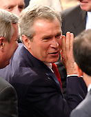 United States President George W. Bush seems to share a private thought with an unidentified member of Congress as he departs the United States House Chamber in the Capitol in Washington, D.C. after delivering his State of the Union Address on January 20, 2004.<br /> Credit: Ron Sachs / CNP