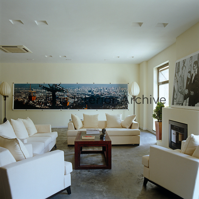 The sitting room is furnished with white sofas and armchairs on a simple concrete floor with the photographic artwork 'Mirage' by Miao Xiaochun and the 'East-West Handshake' by Shi Xinning over the fireplace