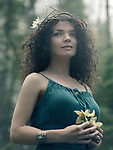 Romantic outdoor portrait of a beautiful young woman with a dreamy serene look on her face wearing a wreath made of tree branches and a green dress holding a wild flower in her hands