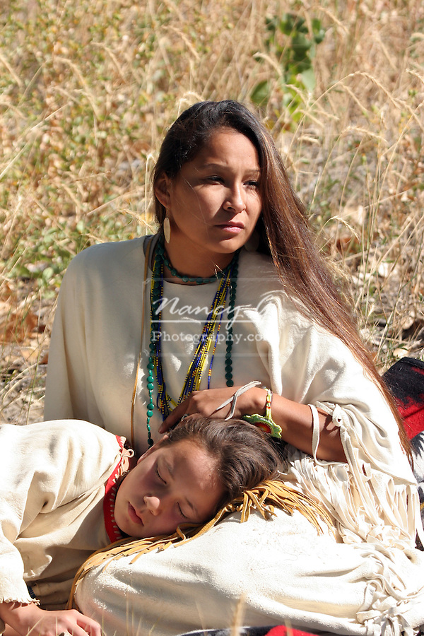 Young Native American Sioux Indian mother and daughter sitting on a blanket in South Dakota