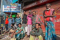 Bangladesh, Jhenaidah. Day laborers with their tools, both men and women, standing on the side of the road looking for work.