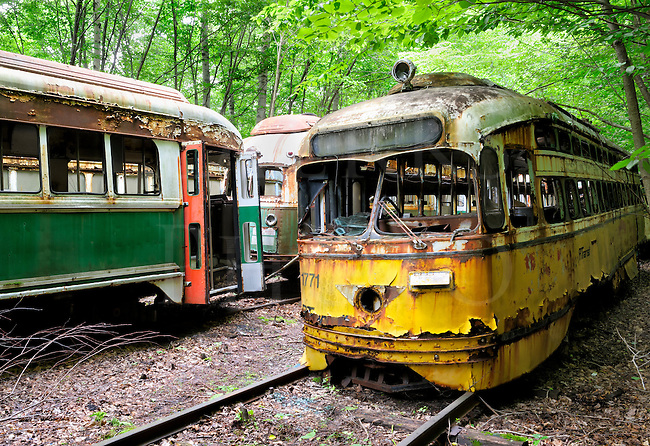 Rusty yellow Pittsburgh PCC trolley sitting abandoned in the woods with her sisters...green trolleys from the Boston T Line...