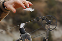00105-044.18 Bowhunting: Close-up of archers hand pulling wind detector from container attached to bow quiver.  Scent, breeze.  H0E1