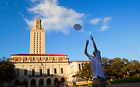 Students play frisbee in the courtyard as the University Of Texas Tower stands overhead