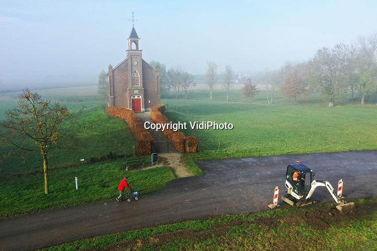 Foto: VidiPhoto<br /> <br /> HOMOET – Het piepkleine terpkerkje (1869) in het Betuwse buurtschap Homoet, maandag in de mist. De Betuwe had maandag last van een hardnekkige mist die voor de nodige verkeersoverlast zorgde. Ook in de nacht van maandag op dinsdag en dinsdag overdag wordt er in grote delen van het land mist verwacht. Daarna overheerst ander herfstweer, met veel regen. Het kerkgebouw in Homoet is een zogenoemd Waterstaatskerkje, de enige nog in de Over-Betuwe, dat in de 19e en begin 20e eeuw diende als vluchtheuvel voor boeren bij hoogwater. De kerk is eigendom van de Hervormde gemeente Valburg-Homoet en wordt iedere eerste zondagochtend van de maand nog gebruikt voor de eredienst.