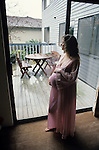 Pregnant mature woman standing by window looking out sliding glass doors and touching her baby Lynnwood Washington State USA MR.