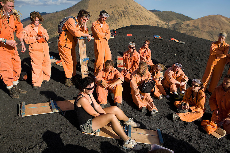 Group of backpackers receive instructions on how to volcano board by the Bigfoot hostel guide on the top of active volcano Cerro Negro, Nicaragua
