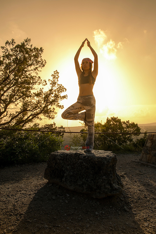 A young woman doing beautiful yoga pose tree, sunset silhouette on Mount Bonnell overlooking the Austin, Texas hill country with yellow sky and clouds with sun sunlight background. Healthy lifestyle successful fitness exercise concept.