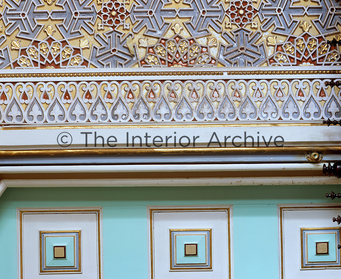 A detail of the neo-classical painted wood panelled walls and the Moorish painted stucco