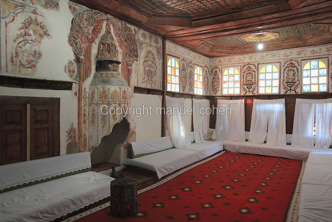 Ceremonial reception room on the 3rd floor of the Zekate House, a grand fortified tower house built 1811-12 with twin towers and a great double arched facade, built and owned by Beqir Zeko, a general administrator of Ali Pasha's government, Gjirokastra, Southern Albania. This large and elaborately decorated room was used for the most important social occasions. The frescoes of garlands of fruits and flowers is typical of the Tulip period of Ottoman architectural design and has symbolic meanings for the health, wealth and abundance of the household. Gjirokastra was settled by the Greek Chaonians, the Romans and Byzantines before becoming an Ottoman city in 1417. Its old town was listed as a UNESCO World Heritage Site in 2005. Picture by Manuel Cohen