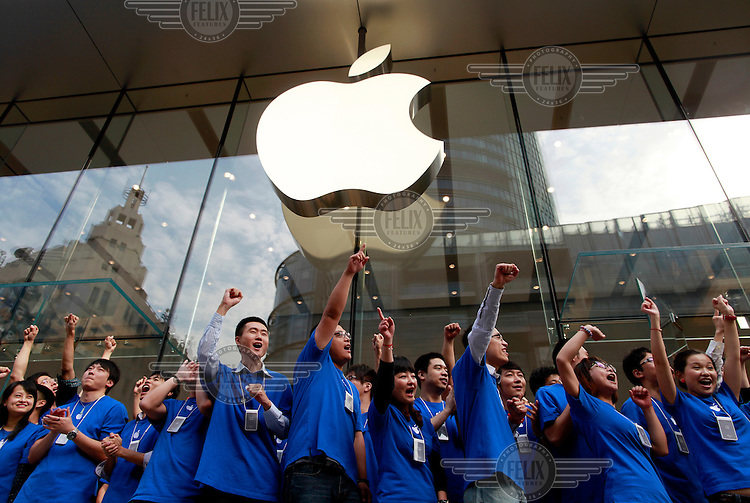 Enthusiastic employees cheer and greet customers at a newly opened flagship Apple Store.