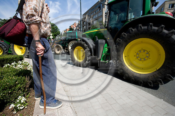 BRUSSELS - BELGIUM - 18 JUNE 2008 -- Hundreds of Farmers from belgian Wallonia went with their tractors to brussels to protest against high fuel cost the day before an EU summit to push leaders for help coping with skyrocketing fuel prices. Here tractors passing an man with a stick in a roundabout with flowers.  Photo: Erik Luntang/EUP-IMAGES