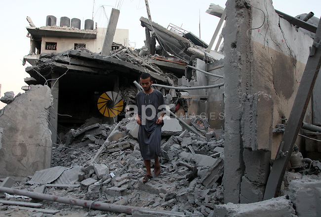 A Palestinian man inspects a destroyed buildings in the Jabalia refugee camp in the northern Gaza Strip on August 8, 2014. Israel launched air strikes across the Gaza Strip on Friday in response to Palestinian rockets fired after Egyptian-mediated talks failed to extend a 72-hour truce in the month-long war. Photo by Ezz Zanoun