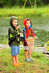 Two young boys fishing in a pond in the summer in northeast PA in the rain.
