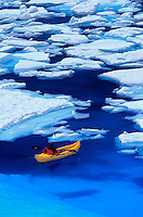 Glacier guide uses a small inflatable kayak to explore the Caribean-like blue waters on a melt pond on the Juneau Ice field in Alaska.