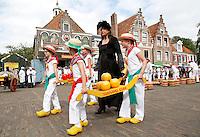 Nederland Edam 2015 07 22 .  Kaasmarkt in Edam . Kinderen dragen een berrie vol kaas. Vrouw loopt in historische klederdracht